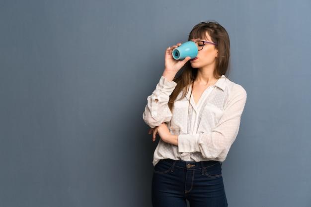 Frau mit den gläsern, die einen heißen tasse kaffee halten