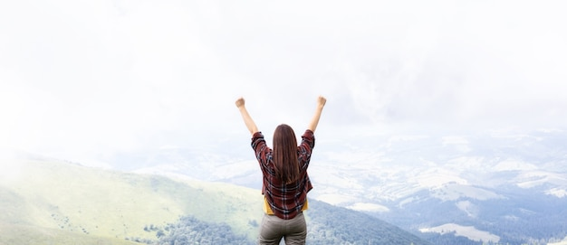 Frau mit den händen oben, die oben auf berg stehen und das sichtfreiheitskonzept genießen
