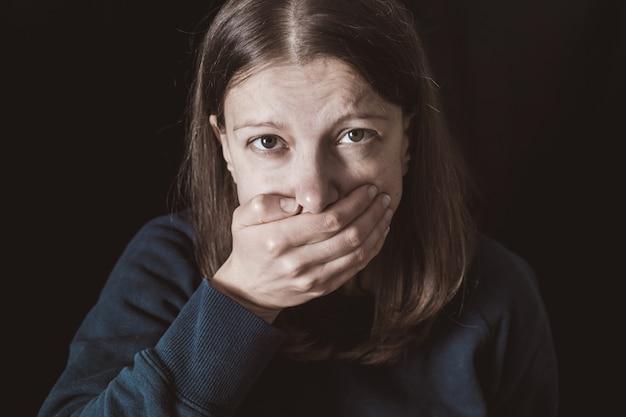 Frau mit den händen schloss mund. gewalt an frauen.