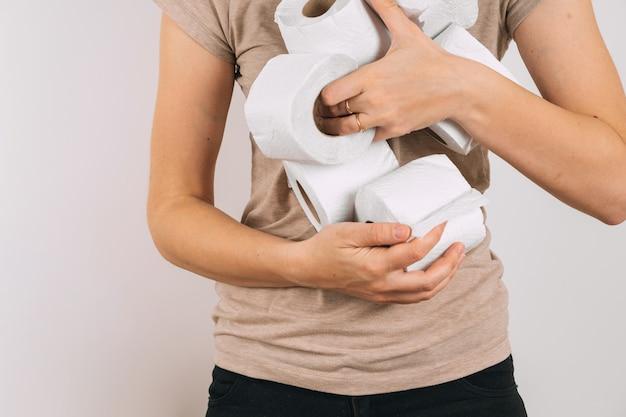 Frau mit den händen voll von toilettenpapierrollen.