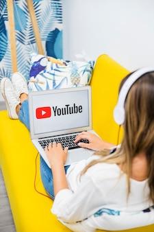 Frau mit den kopfhörern, die im laptop aufpassen