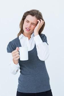 Frau mit den kopfschmerzen, die becher auf weißem hintergrund halten