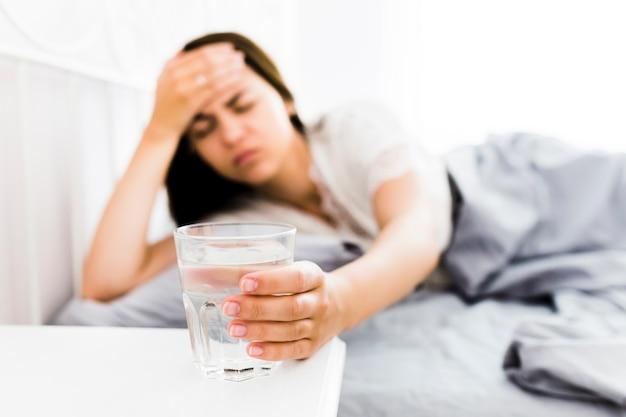Frau mit den kopfschmerzen, die glas wasser nehmen