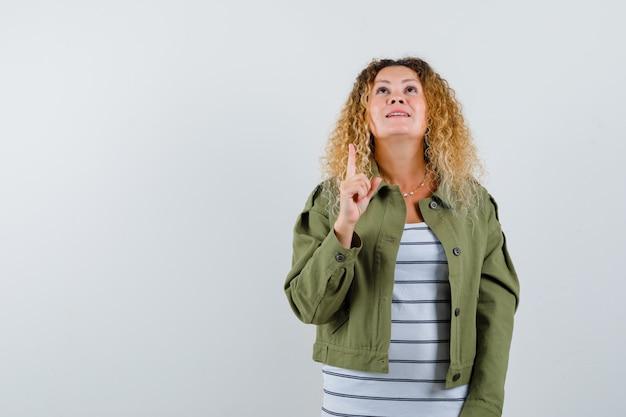 Frau mit den lockigen blonden haaren, die in der grünen jacke nach oben zeigen und hoffnungsvoll aussehen. vorderansicht.