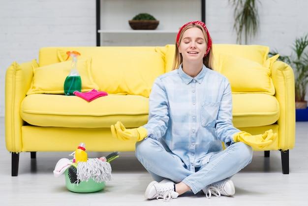 Frau mit den reinigungshandschuhen, die yoga tun