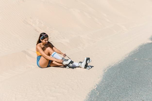 Frau mit den rochen, die auf dem sand sitzen
