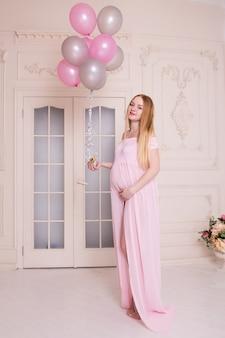 Frau mit den rosa und grauen luftballonen in ihren händen. mutterschafts-, schwangerschafts- und erwartungskonzept.