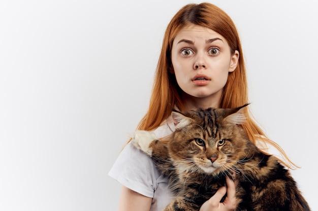 Frau mit den roten haaren, die eine katze halten