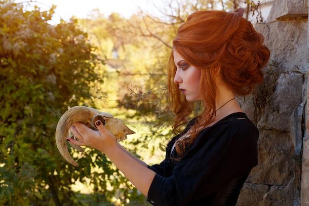 Frau mit den roten haaren, die einen schädel mit hörnern halten