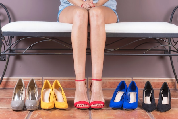 Frau mit den vollkommenen dünnen beinen, versuchend auf verschiedenen schuhen des hohen absatzes. einkaufskonzept