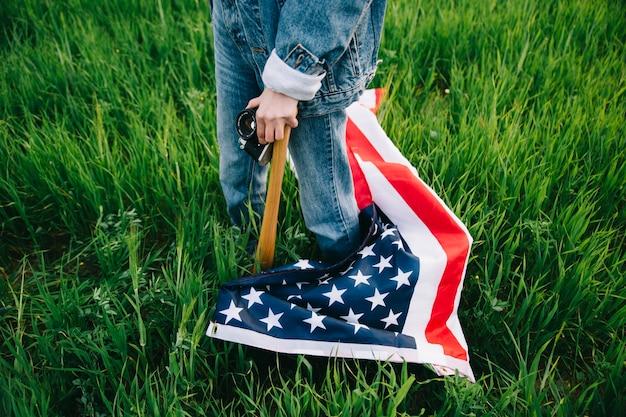 Frau mit der amerikanischen flagge, die auf gras bleibt