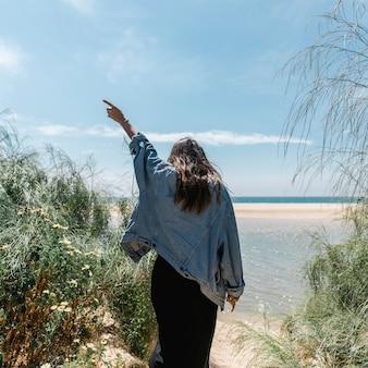 Frau mit der angehobenen hand, die in den tropischen büschen steht