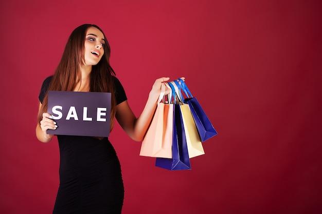 Frau mit der aufschrift black friday und geschenktüten auf rotem grund