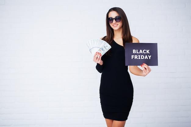 Frau mit der aufschrift black friday und geschenktüten