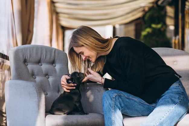 Frau mit der bulldogge, die in einem café sitzt