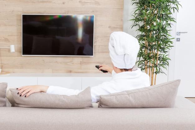 Frau mit der fernbedienung, die auf couch sitzt