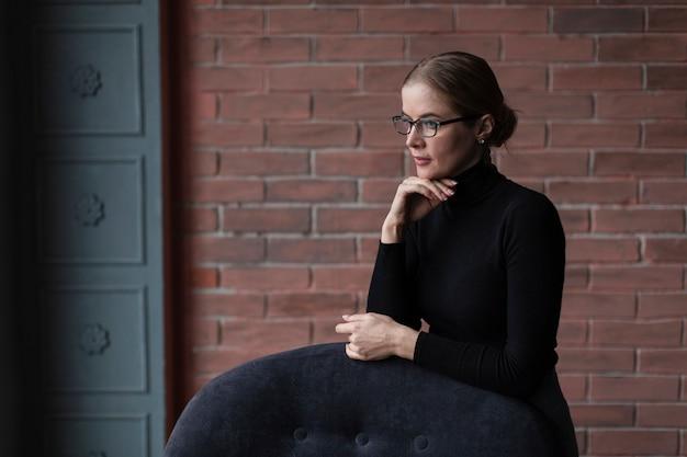 Frau mit der formellen kleidung, die auf couch sitzt
