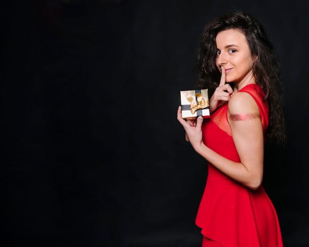 Frau mit der geschenkbox, die geheime geste zeigt