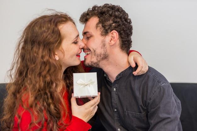Frau mit der geschenkbox, die mann umarmt