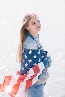 Frau mit der geschlossenen augenstellung eingewickelt in wellenartig bewegender amerikanischer flagge