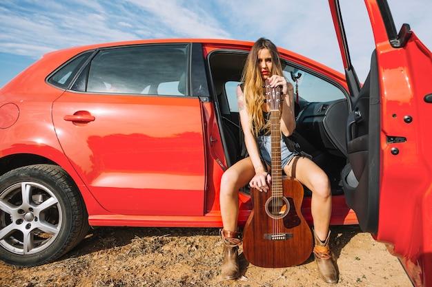 Frau mit der gitarre, die im auto balanciert