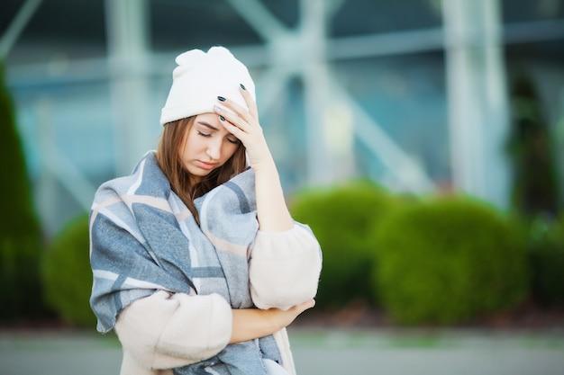 Frau mit der grippe, die draußen einen schal trägt