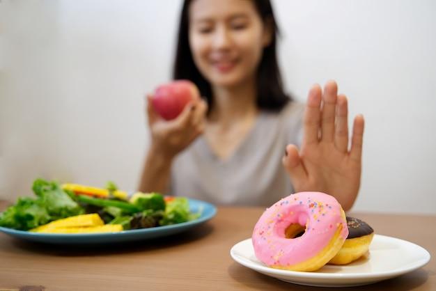 Frau mit der hand lehnen sie junk food ab, indem sie ihre lieblingskrapfen herausdrücken und roten apfel und salat für gute gesundheit wählen.
