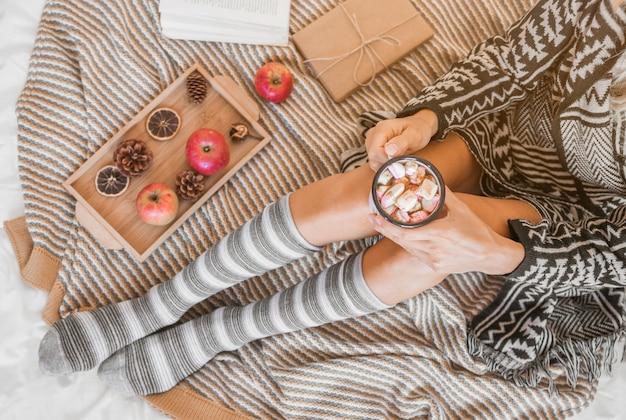 Frau mit der heißen schokolade, die auf bett sich entspannt