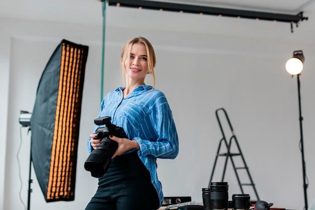 Frau mit der kamera, die das studio für ein schießen vorbereitet