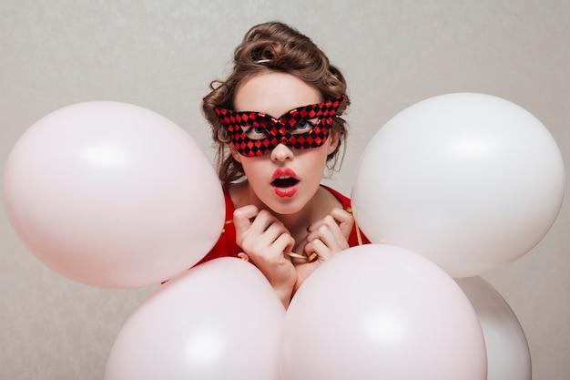 Frau mit der karnevalsmaske, die ballone hält