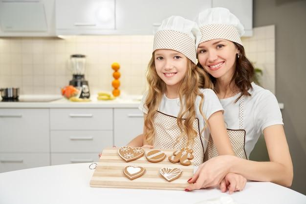 Frau mit der kleinen tochter, die tablett mit keksen hält