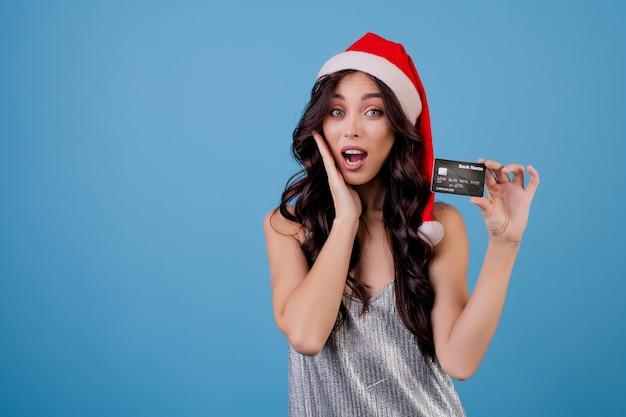 Frau mit der kreditkarte, die sankt-hut trägt