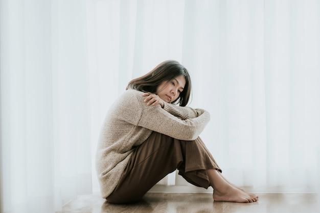 Frau mit der krise, die alleine auf dem boden sitzt