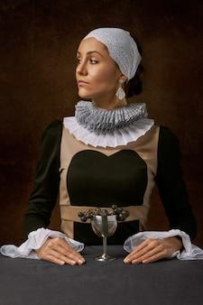 Frau mit der langärmligen oberseite, die seitlich schauen gegenüberstellt