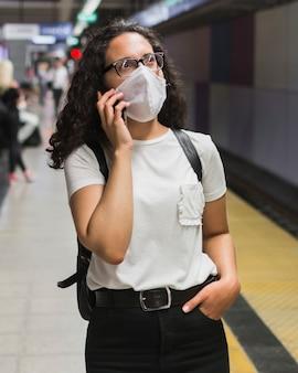 Frau mit der medizinischen maske, die am telefon spricht, während sie auf die u-bahn wartet