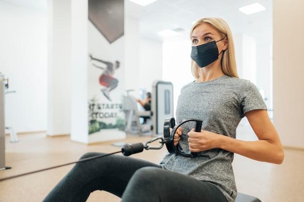 Frau mit der medizinischen maske, die an der turnhalle arbeitet
