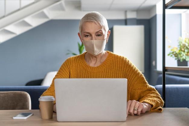 Frau mit der medizinischen maske, die arbeitet