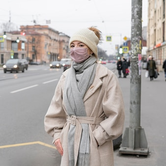 Frau mit der medizinischen maske, die auf den bus in der stadt wartet