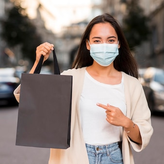 Frau mit der medizinischen maske, die auf einkaufstasche hält und zeigt