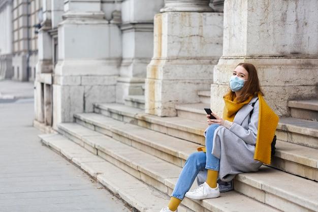 Frau mit der medizinischen maske, die auf stufen sitzt und smartphone verwendet