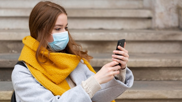 Frau mit der medizinischen maske, die bilder mit smartphone macht