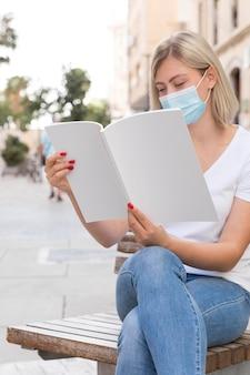 Frau mit der medizinischen maske, die draußen auf bank sitzt und buch liest