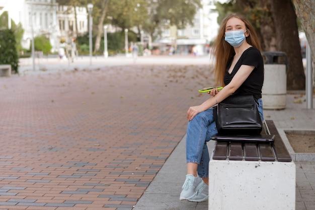 Frau mit der medizinischen maske, die draußen auf einer bank mit kopienraum sitzt
