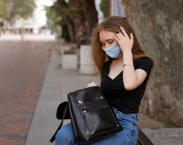 Frau mit der medizinischen maske, die draußen auf einer bank sitzt