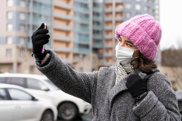 Frau mit der medizinischen maske, die ein selfie in der stadt nimmt