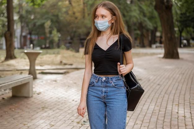 Frau mit der medizinischen maske, die im park geht
