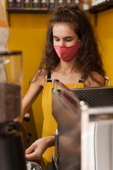 Frau mit der medizinischen maske, die in einem kaffeehaus arbeitet