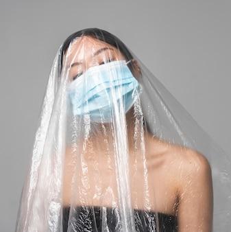Frau mit der medizinischen maske, die in plastik bedeckt wird