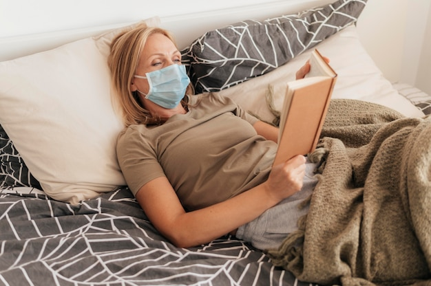Frau mit der medizinischen maske, die in quarantäne zu hause liest