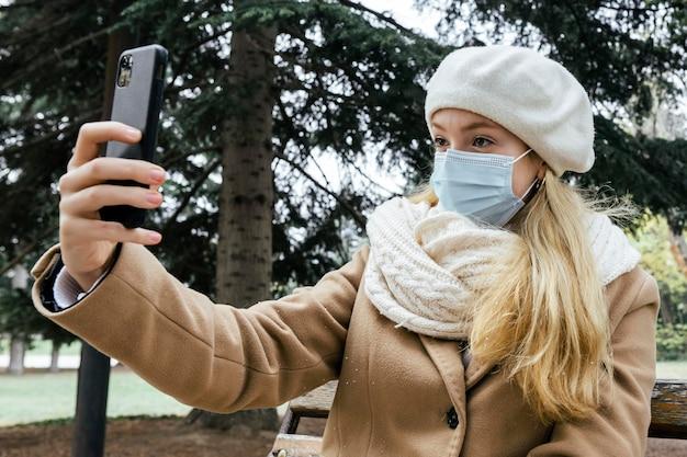 Frau mit der medizinischen maske, die selfie im park während des winters nimmt